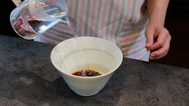 器にスープの素とお湯を注ぐ