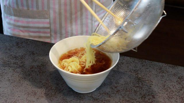 茹でた麺を器に入れる